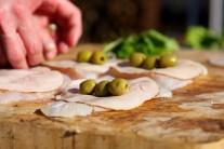 Na plátky šunky poukladáme zelené olivy.