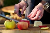 Ďalej jablká naplníme hrozienkami a orechami podľa chuti, pokvapkáme medom a navrch položíme kúsok masla.