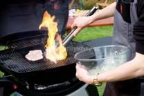 Názorná ukážka vkladania neodkvapkaného mäsa na gril a následné vzplanutie.