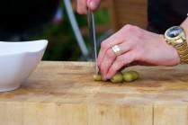 Pri krájaní olív dbáme na to, aby sme mali kúsky rovnomerné. U plnených olív vmiešame aj nasekanú papričku, ktorá tvorí náplň olivy. Pre obmenu môžeme použiť aj ďalšie druhy olív.