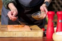 K potieraniu filetu použijeme silikónový štetec alebo iba lyžičku. Potretý filet lososa odložíme nabok. Vyberieme z vody cédrovú doštičku a zľahka ju osušíme.