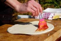 Cesto presunieme na kovovú tácku a potrieme ho paradajkovou zmesou.
