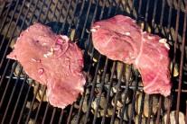 Detail mäsa na grile aj so zvyšnou marinádou.