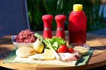 Zo všetkého najskôr si pripravíme všetky potrebné suroviny. Na hovädzí hamburger budeme potrebovať minimálne 750 gramov hovädzieho mletého mäsa, slaninu, syr, paradajky, ľadový šalát, cibuľu, kečup, horčicu, alebo i majonézu.