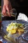 Naskladané zemiaky s cibuľou, osolené a okorenené pokvapkáme olejom. Môžeme pridať ešte aromatické zelené bylinky ako tymián a rozmarín, ktoré dodajú zemiakom intenzívnu vôňu.