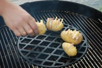 Rozkrojené zemiaky naplnené syrom a slaninou pokladáme na rozpálený rošt čo najbližšie k stredu.