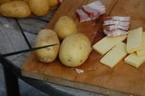 Teraz narežeme zemiaky tak, aby sa do vzniknutého priestoru dala zasunúť slaninka a syr.