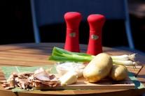 Na zemiaky pečené v dyme budeme potrebovať 4 rovnako veľké zemiaky, slaninu, maslo, kyslú smotanu, jarné cibuľky, soľ a korenie.