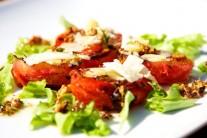 Grilované paradajky posypeme vyprážaným cesnakom a hoblinkami parmezánu. Doplniť ich môžeme ľadovým šalátom a opečenými bagetkami.