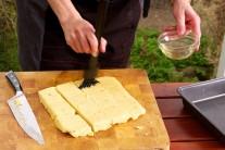 Polentu dáme do plytkého pekáča, prikryjeme alobalom alebo potravinárskou fóliou a necháme tak na 4 hodiny vychladnúť. Vychladnutú polentu nakrájame na rovnako veľké kusy a potrieme ju olivovým olejom.