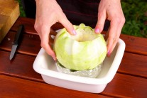 Vydlabanú hlávku kapusty spevníme alobalom a vložíme do zapekacej misky.