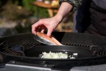 Vo chvíli, kedy začneme smažiť cibuľku, pridáme rozotrený alebo prelisovaný cesnak. Zároveň položíme na rozpálený grilovací rošt porcie lososa a grilujeme z každej strany po dobu 6 minút.