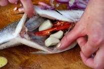 Rybu nasolíme zvnútra aj zvonku, do brušnej dutiny vložíme cesnak a čili papričku. Ďalej pridáme po vetvičke rozmarínu a tymianu. Rybu zvonku potrieme trochou oleja.