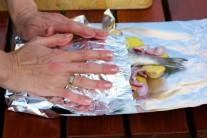 Alobal prehneme cez rybu so zemiakmi, pevne uzavrieme a zabalíme do úhľadného balíčka.