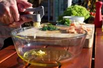Do sklenenej misy nalejeme olivový olej a pridáme prelisovaný cesnak.